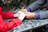 couple holding hands across table closeup